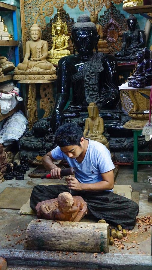 Een mens beitelt hout in een beeldhouwwerk stock foto
