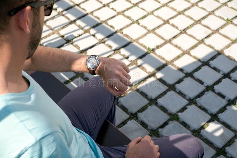 Een mens bekijkt zijn horloge in de straat royalty-vrije stock afbeelding