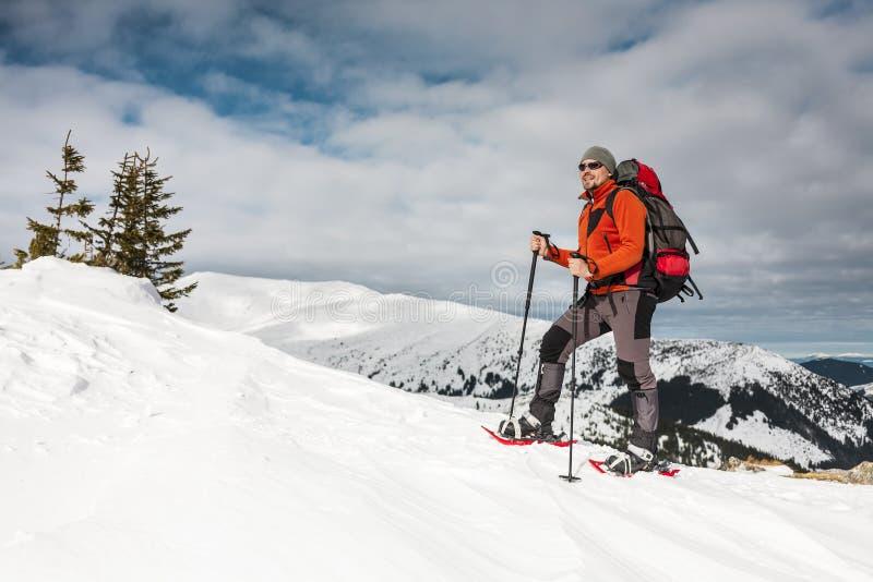 Een mens beklimt tot de bovenkant van de berg stock fotografie