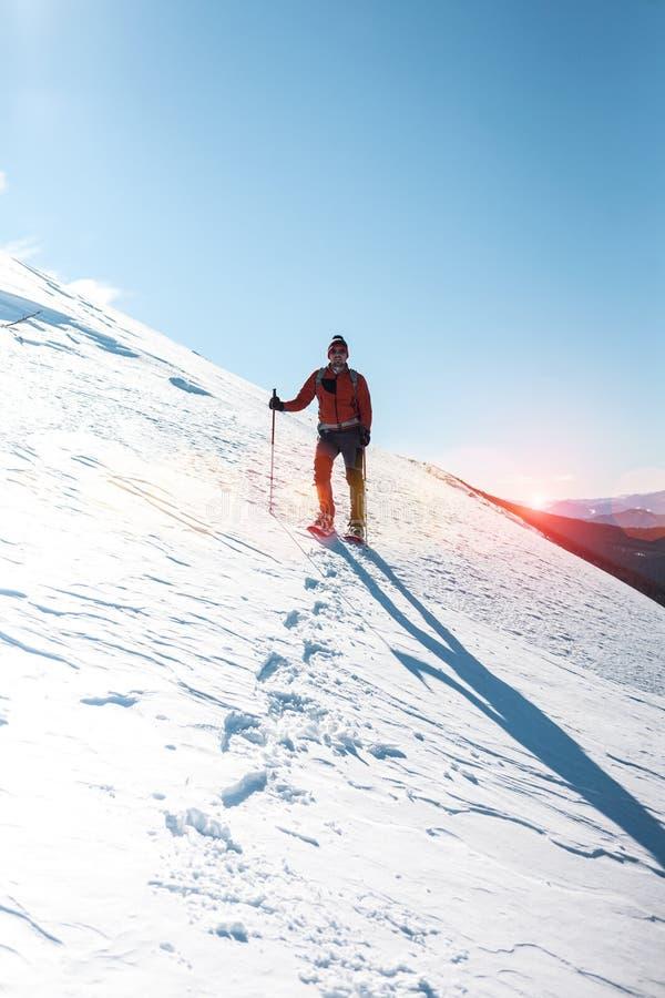 Een mens beklimt tot de bovenkant van de berg stock foto
