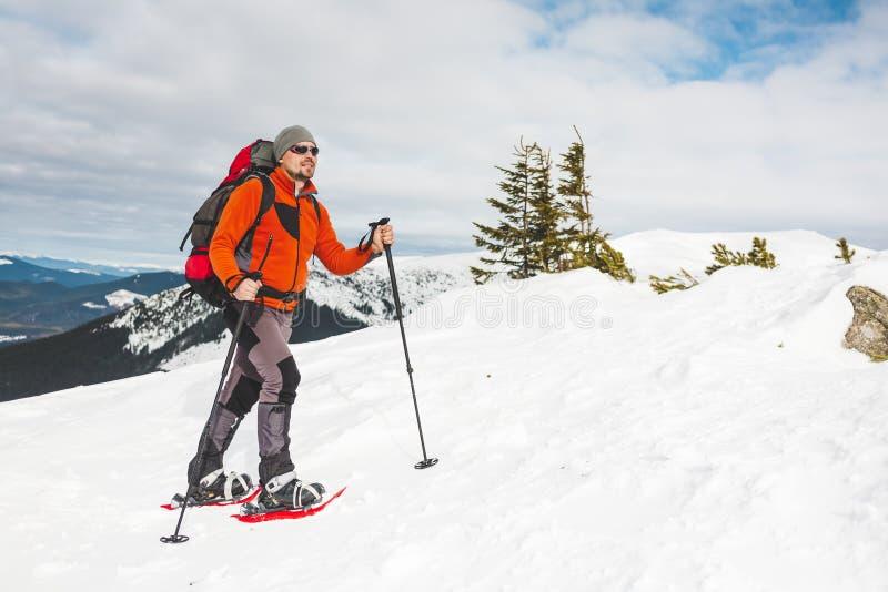 Een mens beklimt tot de bovenkant van de berg royalty-vrije stock afbeeldingen