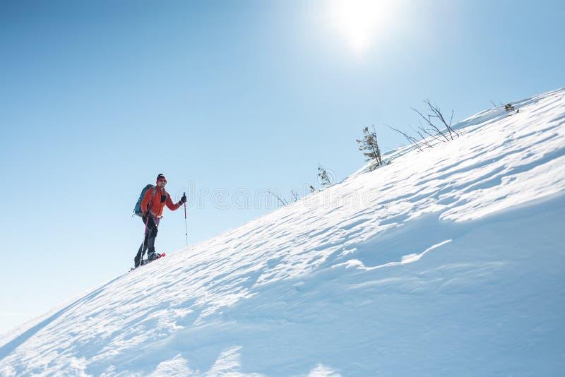 Een mens beklimt tot de bovenkant van de berg royalty-vrije stock fotografie