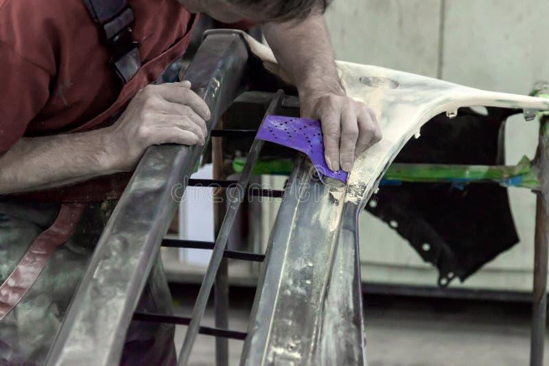 Een mens bereidt een element van het autolichaam voor het schilderen na een ongeval voor royalty-vrije stock afbeelding