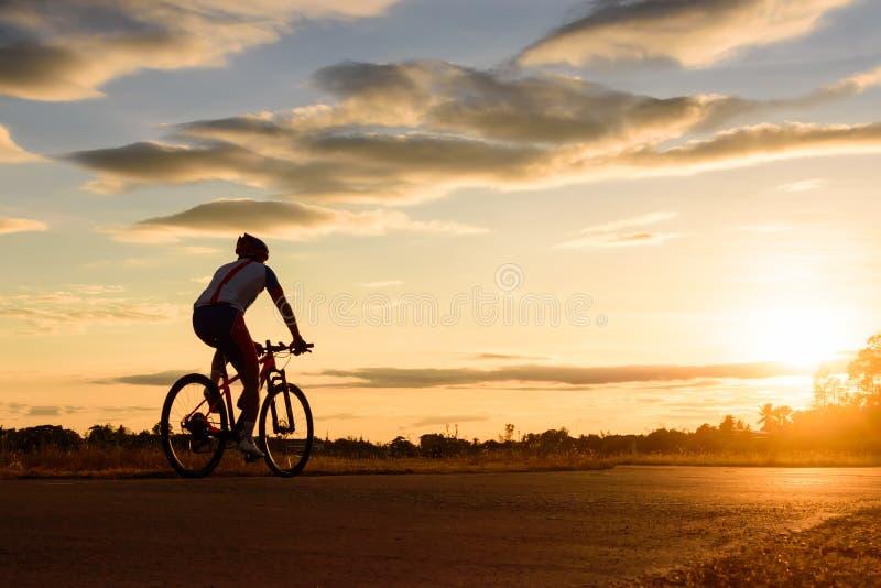 Een mens berijdt een fiets bij zonsondergang met zonnestraal stock afbeelding