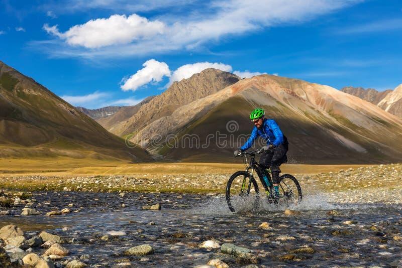 Een mens berijdt een fiets in de bergen Kyrgyzstan De Vallei van de Burkanrivier stock afbeeldingen