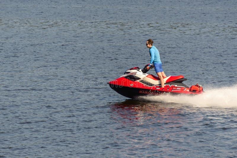 Een mens berijdt een rode straalski op de rivier stock afbeelding