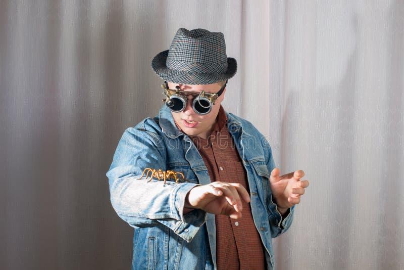 Een mens in beschermende brillen bekijkt de spinzitting op zijn wapen, steampunk stijl stock fotografie