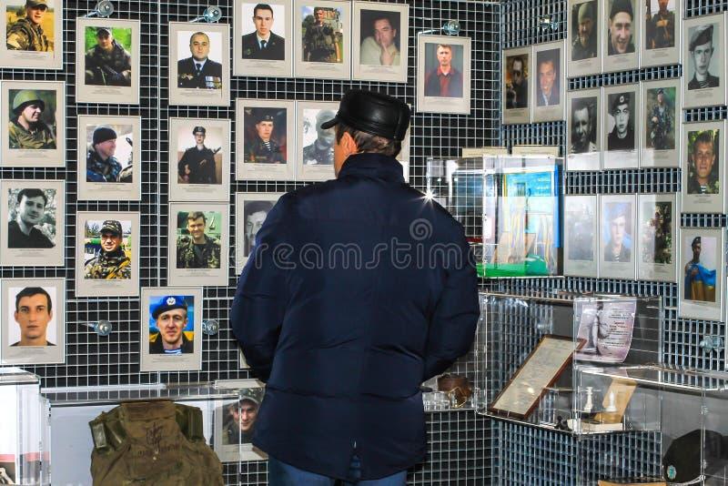 Een mens bevindt zich dichtbij een tribune met foto's van dode militairen, vechters van het Oekraïense Leger, in het Museum van A stock fotografie