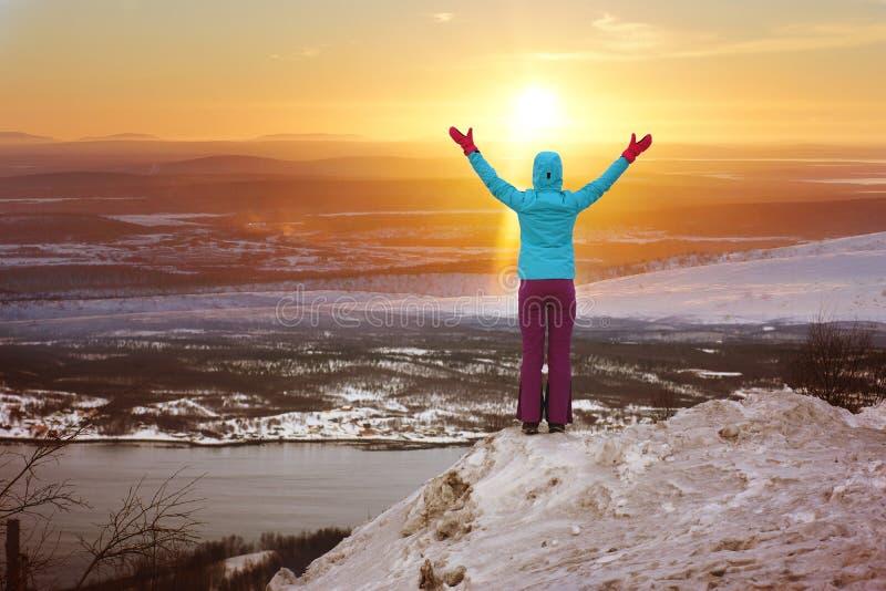 Een mens bevindt zich op een berg in de winter en hief zijn handen op, die de zon, een mooi landschap vooruit begroeten royalty-vrije stock foto's