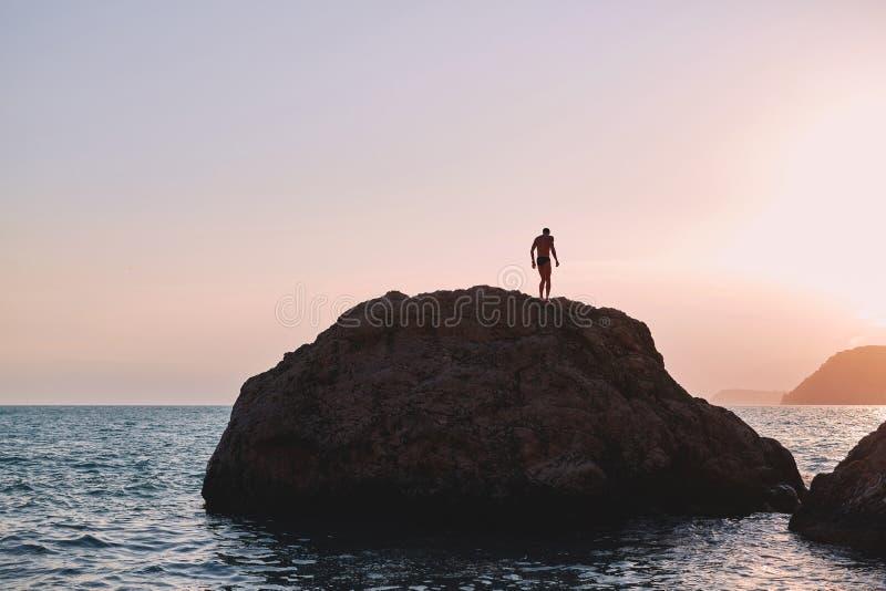 Een mens bevindt zich op een grote rots in het overzees bij zonsondergang royalty-vrije stock foto's