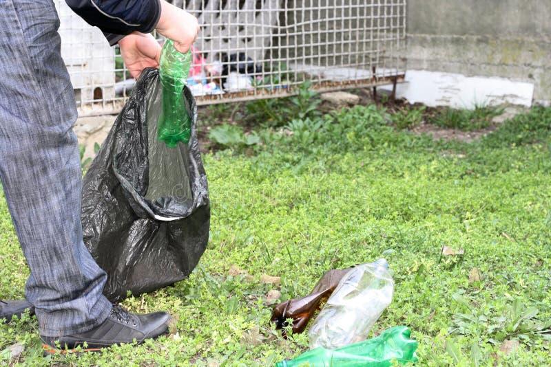 Een mens is bezig geweest met de ecologie van aard en verzamelt plastic flessen in een plastic zak die de grond schoonmaakt stock foto