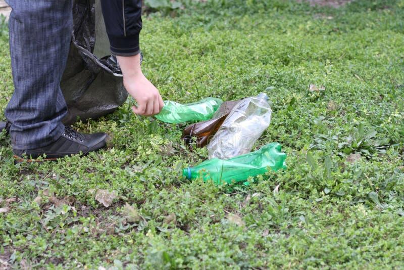 Een mens is bezig geweest met de ecologie van aard en verzamelt plastic flessen in een plastic zak die de grond schoonmaakt stock foto's