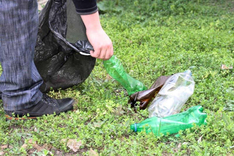 Een mens is bezig geweest met de ecologie van aard en verzamelt plastic flessen in een plastic zak die de grond schoonmaakt royalty-vrije stock afbeelding