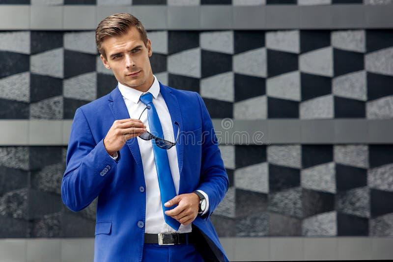 Een mens in een blauw kostuum tegen een achtergrond van donkere moderne architectuur stock fotografie