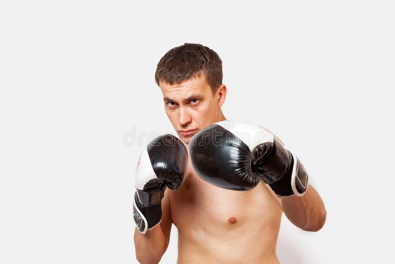 Een mens in bokshandschoenen met kneuzingen op lichaam en gezichtssteken tijdens een strijd en in dozen doend op een wit isoleerd royalty-vrije stock afbeelding