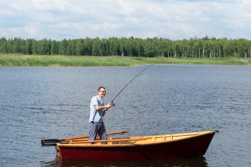 Een mens in een boot op een rivier verheugt zich wanneer een vis het gevangen spinnen terwijl trekkend het uit het water is royalty-vrije stock afbeelding
