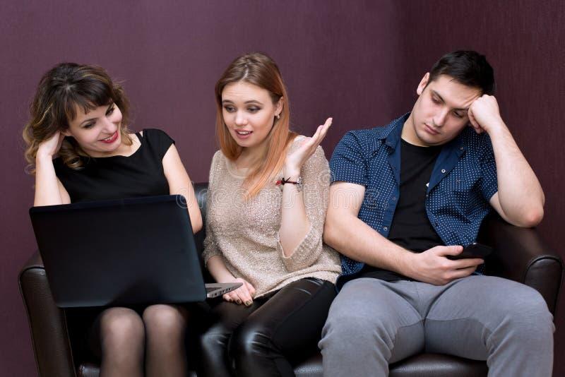 Een mens is bored met twee meisjes die op een film letten stock afbeelding