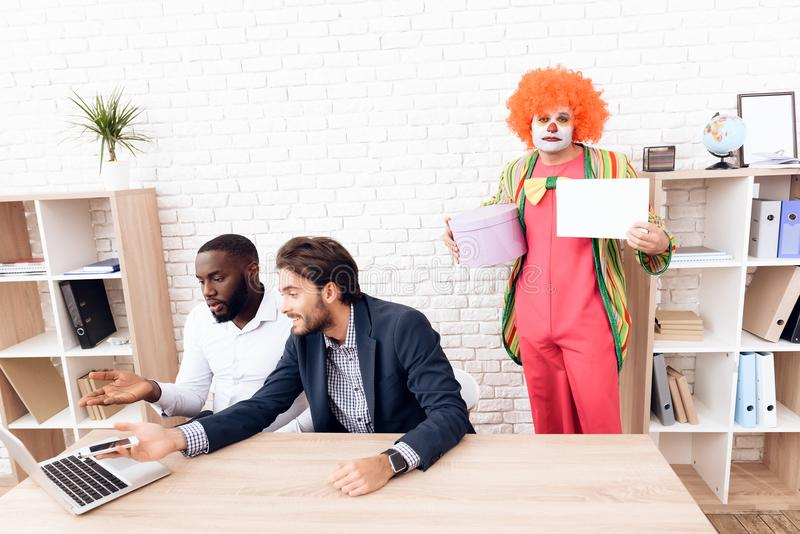 Een mens in een clownkostuum bevindt zich naast andere mensen in een helder bedrijfsbureau op Dwazen` Dag stock afbeelding