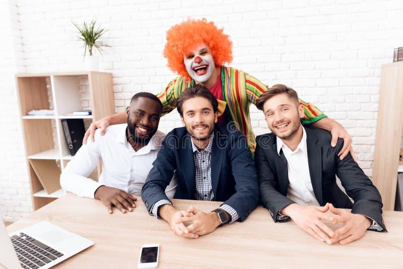 Een mens in een clownkostuum bevindt zich naast andere mensen in een helder bedrijfsbureau op Dwazen` Dag royalty-vrije stock fotografie