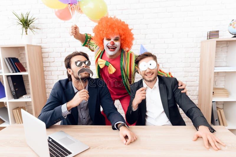 Een mens in een clownkostuum bevindt zich naast andere mensen in een helder bedrijfsbureau op Dwazen` Dag royalty-vrije stock afbeeldingen