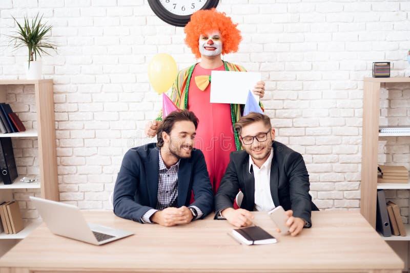 Een mens in een clownkostuum bevindt zich naast andere mensen in een helder bedrijfsbureau op Dwazen` Dag royalty-vrije stock afbeelding