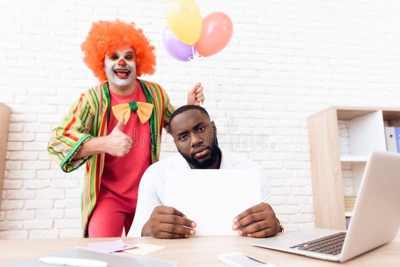 Een mens in een clownkostuum bevindt zich naast een zwarte mens die bij zijn bureau zit stock foto's