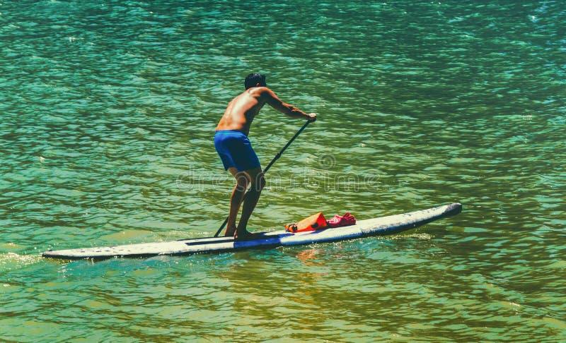 Een mens corssing de rivier en oefent de kajaksport uit stock foto