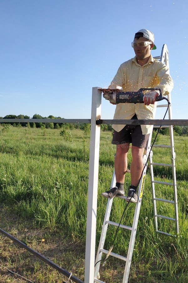 Een mens in de yard snijdt het metaalprofiel op de omheining die zich op de ladder met een hoekmolen bevinden stock fotografie