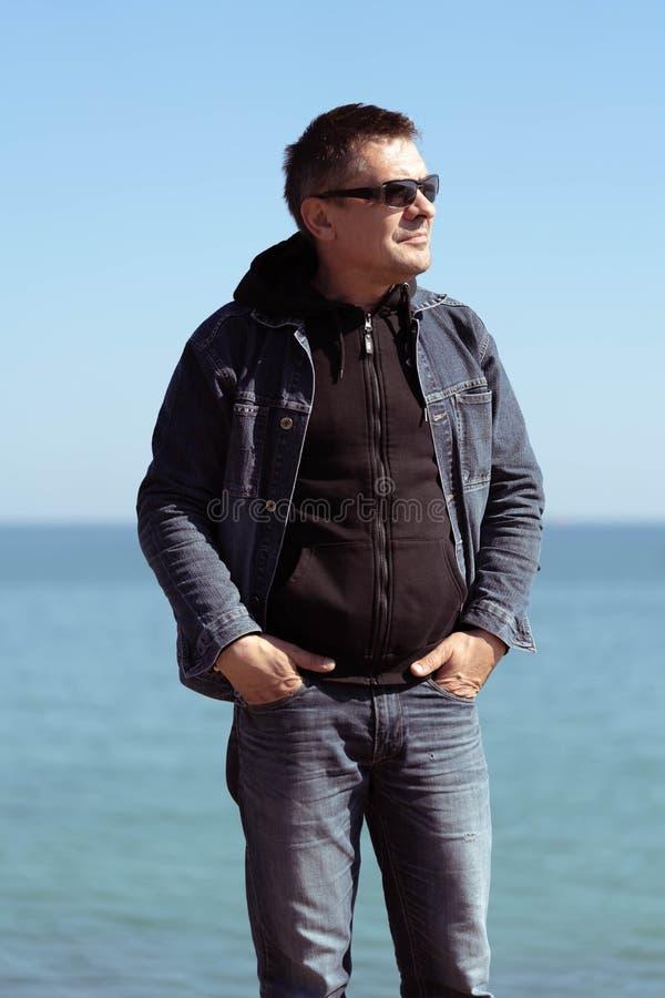 Een mens in een denimkostuum op de achtergrond van het overzees in een de lente zonnige dag stock foto's