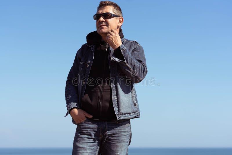 Een mens in een denimkostuum op de achtergrond van het overzees in een de lente zonnige dag stock afbeelding