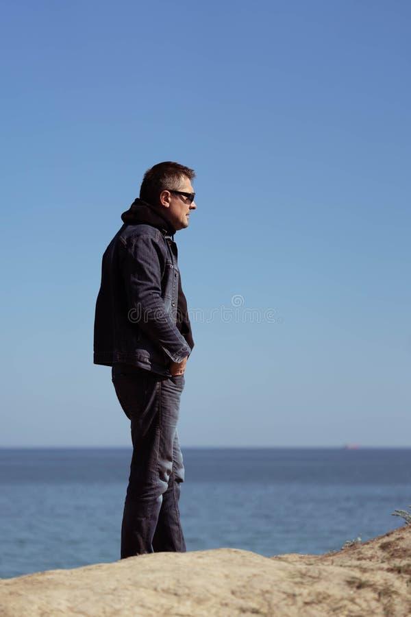 Een mens in een denimkostuum op de achtergrond van het overzees in een de lente zonnige dag stock foto