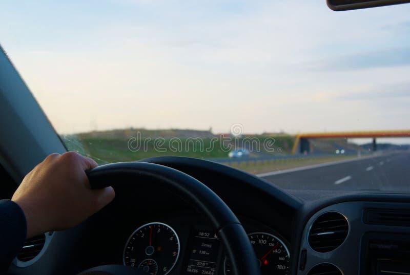 Een mens die een auto achter het wiel drijven stock afbeelding