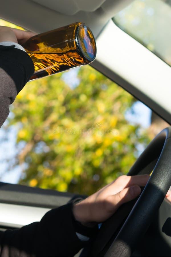 Een mens die een auto drijven drinkt een alcoholische drank van een fles royalty-vrije stock foto