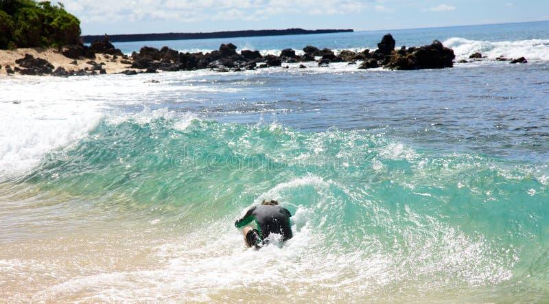Een mens die bij Groot Strand in Maui skimboarding stock foto