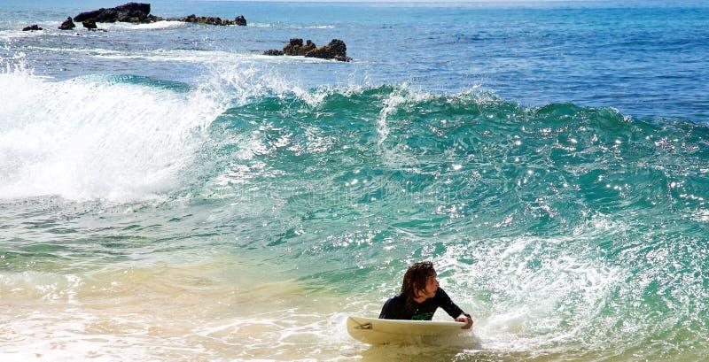 Een mens die bij Groot Strand in Maui skimboarding stock foto's