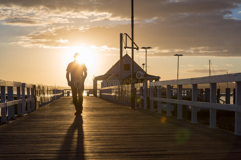 Een mens die bij zonsondergang bij de pijler lopen stock foto