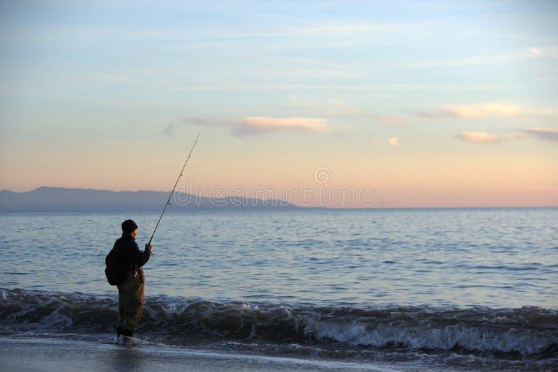 Een mens die bij zonsondergang vist stock fotografie