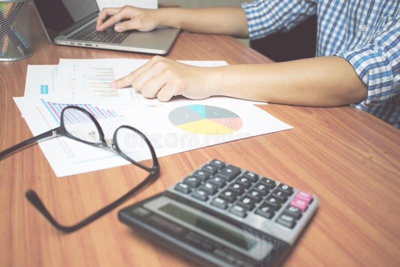 Een mens die een blauw plaidoverhemd dragen werkt aan een bureau bevat met Calculators, oogglazen, computers en documenten royalty-vrije stock fotografie