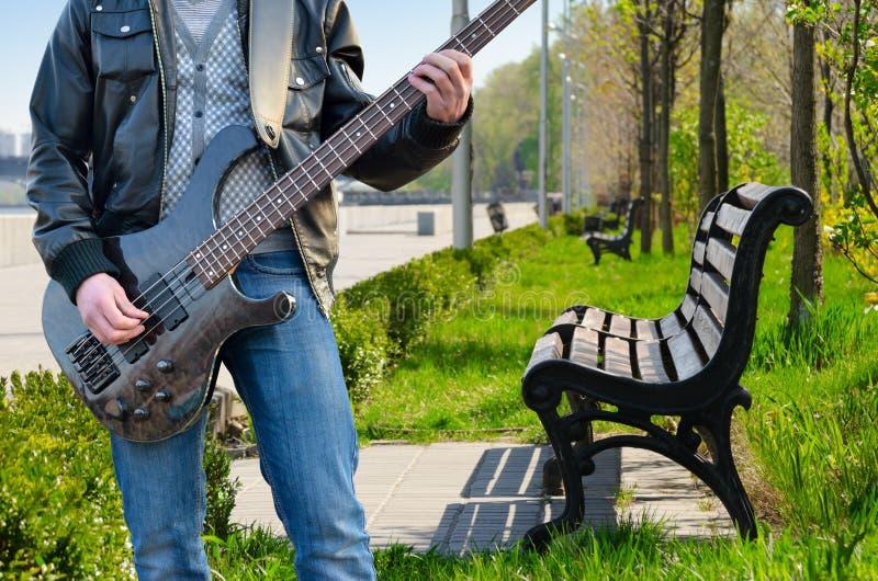 Een mens die de elektrische gitaar in het park spelen stock foto