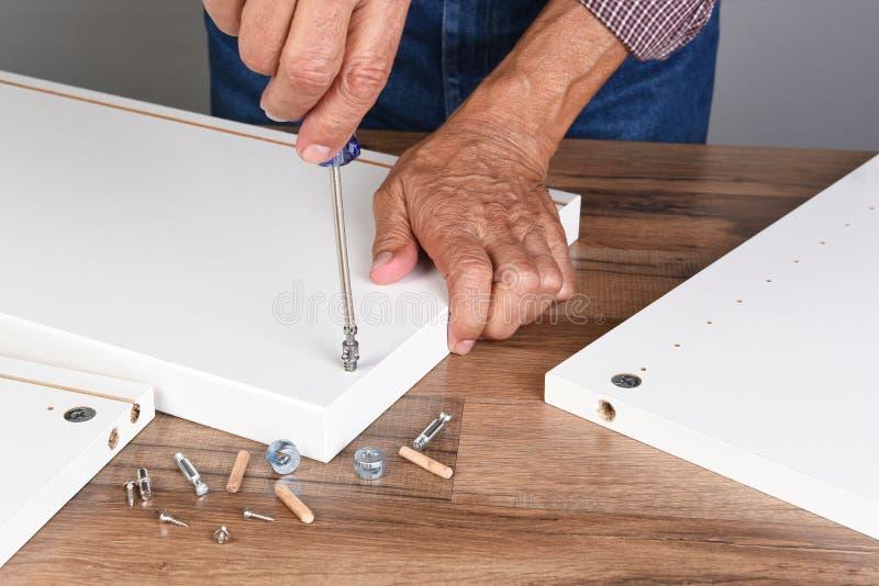 Een mens die een DIY-meubel assembleren De persoon gebruikt een schroevedraaier om een stuk van hardware te installeren royalty-vrije stock foto