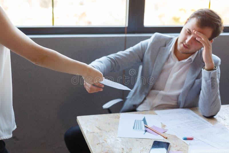 Een mens, die een document houden, dat hij het meisje een beambte geeft Binnen in het bureau royalty-vrije stock fotografie