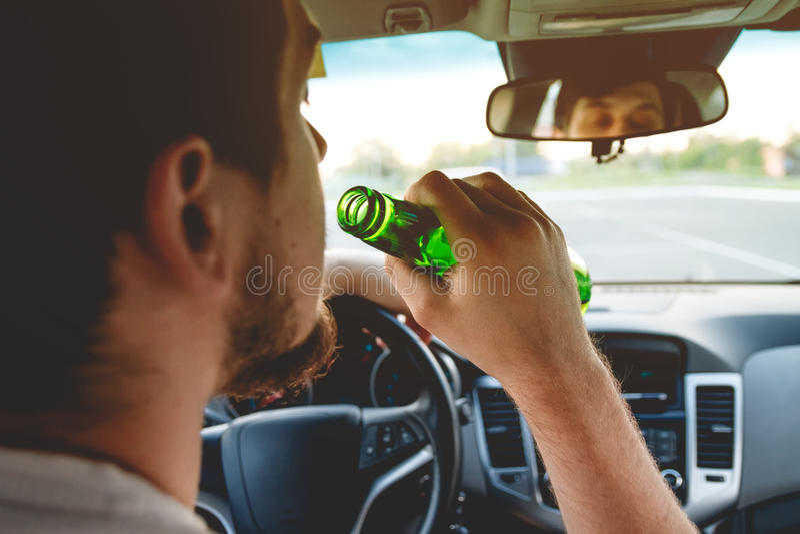 Een mens die een auto met een fles bier drijven royalty-vrije stock afbeeldingen