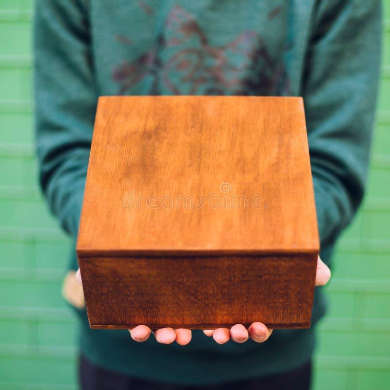 Een mens die een houten doos houden stock fotografie