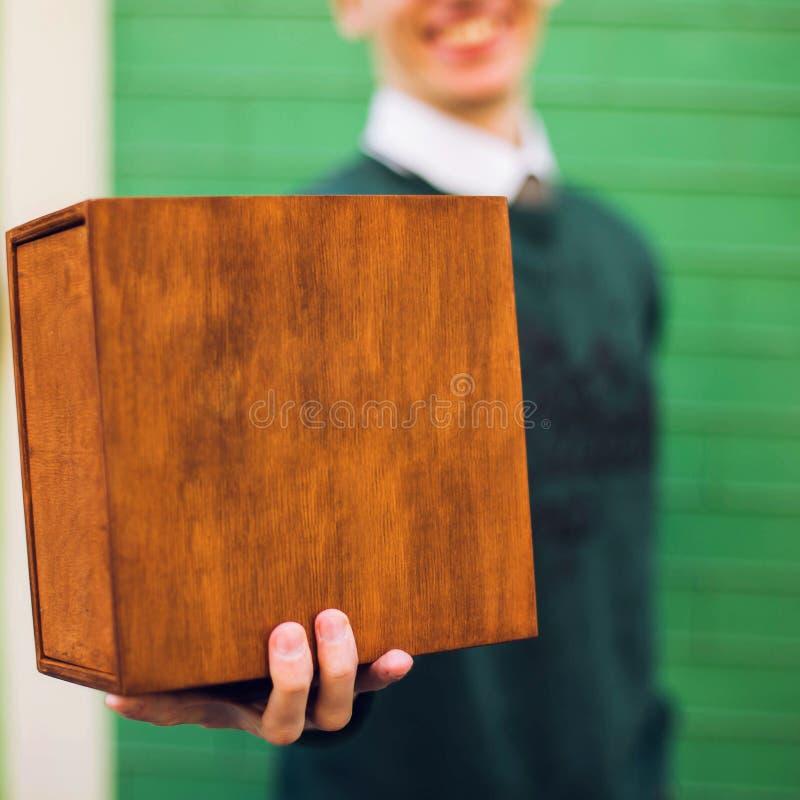 Een mens die een houten doos houden royalty-vrije stock afbeelding