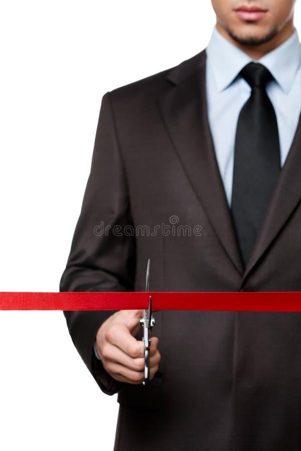 Een mens die een lint snijden stock foto's
