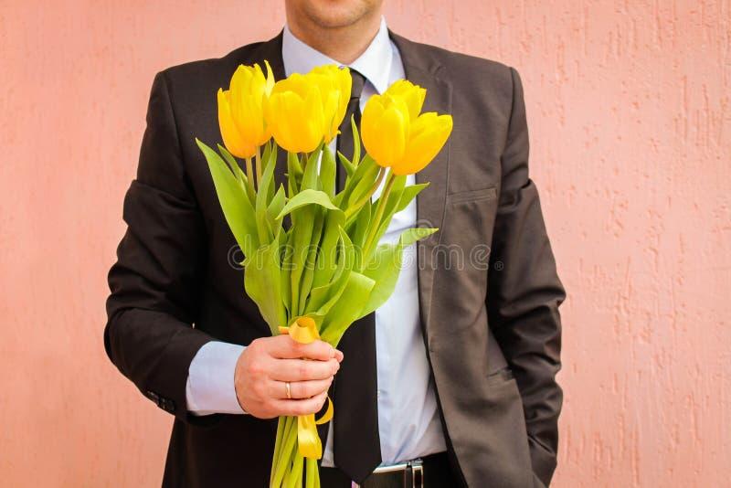 Een mens die een pak dragen, die een boeket van tulpen houden De man geeft een boeket van bloemen stock fotografie