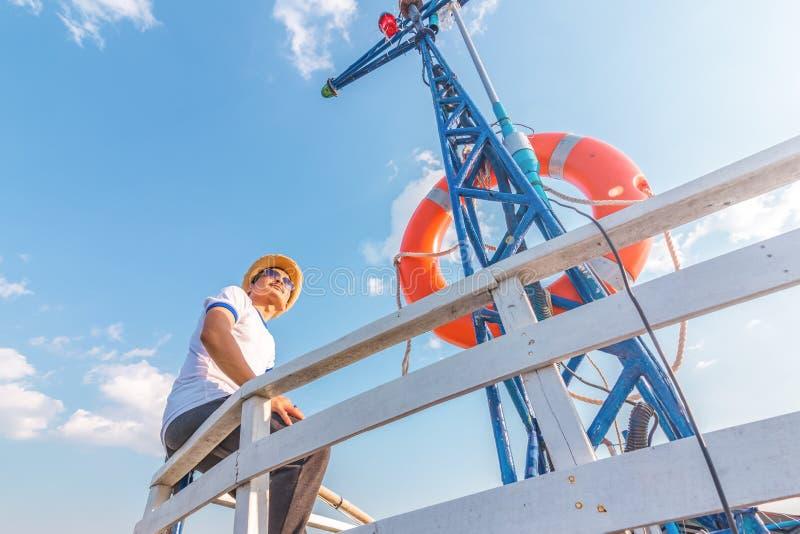 Een mens die gelukkig op het jacht ontspannen die van de vakantiezeilboot een rust op de zomerboot en blauwe hemelachtergrond heb stock afbeelding