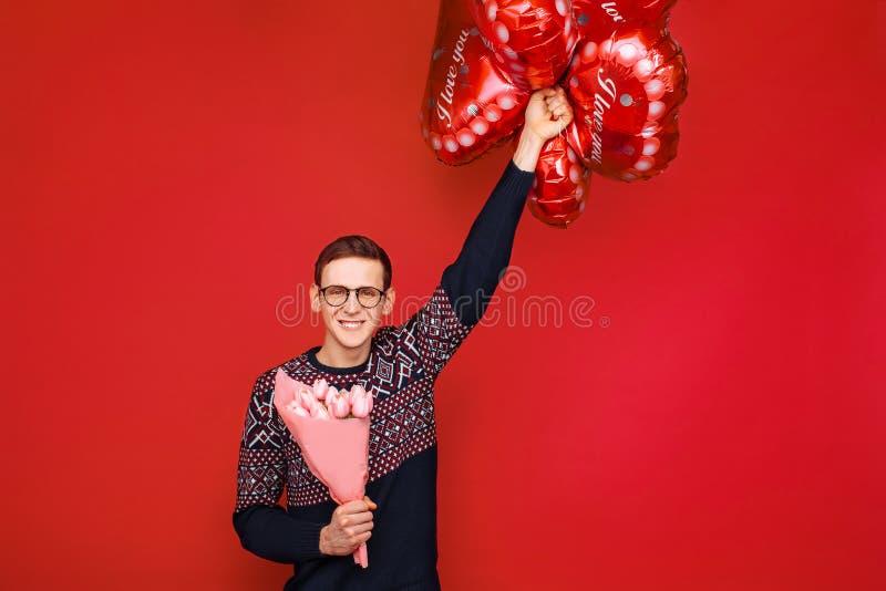 Een mens die glazen met een bos van bloemen en hart-vormige ballons op een rode achtergrond dragen De dag van de valentijnskaart  stock foto's