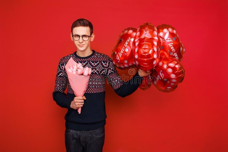 Een mens die glazen met een bos van bloemen en hart-vormige ballons op een rode achtergrond dragen De dag van de valentijnskaart  stock afbeeldingen