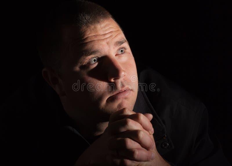 Een mens die met heilig licht bidt stock foto's
